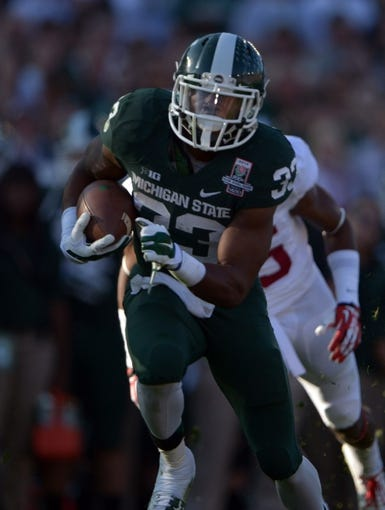 Jan 1, 2014; Pasadena, CA, USA; Michigan State Spartans running back Jeremy Langford (33) carries the ball against the Stanford Cardinal in the 100th Rose Bowl. Mandatory Credit: Kirby Lee-USA TODAY Sports
