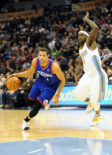 Jan 1, 2014; Denver, CO, USA; Philadelphia 76ers guard Michael Carter-Williams (1) drives past Denver Nuggets guard Ty Lawson (3) in the first quarter at Pepsi Center. Mandatory Credit: Byron Hetzler-USA TODAY Sports