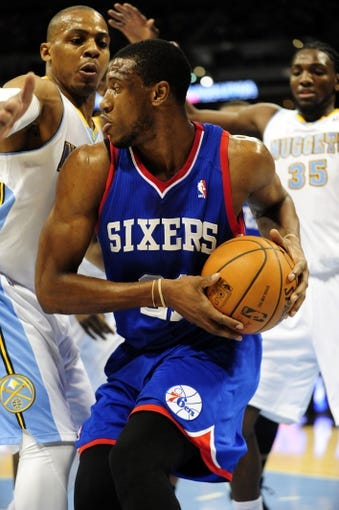 Jan 1, 2014; Denver, CO, USA; Philadelphia 76ers forward Thaddeus Young (21) looks to get past Denver Nuggets guard Randy Foye (4) in the first quarter at Pepsi Center. Mandatory Credit: Byron Hetzler-USA TODAY Sports