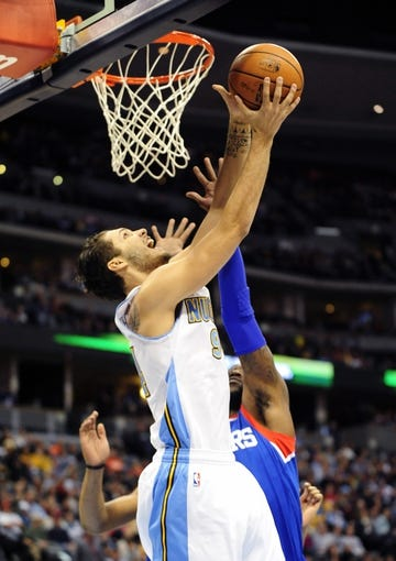 Jan 1, 2014; Denver, CO, USA; Denver Nuggets guard Evan Fournier (94) shoots as Philadelphia 76ers guard Tony Wroten (8) defends in the first quarter at Pepsi Center. Mandatory Credit: Byron Hetzler-USA TODAY Sports