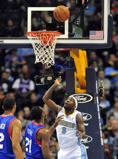 Jan 1, 2014; Denver, CO, USA; Denver Nuggets guard Ty Lawson (3) watches his shot as Philadelphia 76ers forward Thaddeus Young (21) defends in the third quarter at Pepsi Center.  Philadelphia won 114-102. Mandatory Credit: Byron Hetzler-USA TODAY Sports