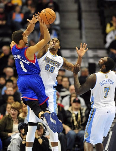 Jan 1, 2014; Denver, CO, USA; Philadelphia 76ers guard Michael Carter-Williams (1) shoots as Denver Nuggets forward Darrell Arthur (00) defends in the fourth quarter at Pepsi Center.  Philadelphia won 114-102. Mandatory Credit: Byron Hetzler-USA TODAY Sports