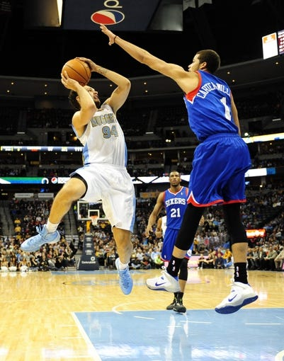 Jan 1, 2014; Denver, CO, USA; Denver Nuggets guard Evan Fournier (94) shoots as Philadelphia 76ers guard Michael Carter-Williams (1) defends in the fourth quarter at Pepsi Center.  Philadelphia won 114-102. Mandatory Credit: Byron Hetzler-USA TODAY Sports