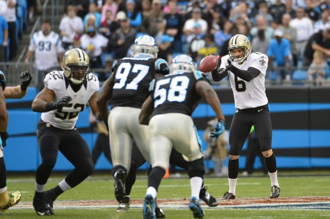 Dec 22, 2013; Charlotte, NC, USA; New Orleans Saints punter Thomas Morstead (6) punts as Carolina Panthers defensive end Mario Addison (97) and outside linebacker Thomas Davis (58) defend in the first quarter at Bank of America Stadium. Mandatory Credit: Bob Donnan-USA TODAY Sports
