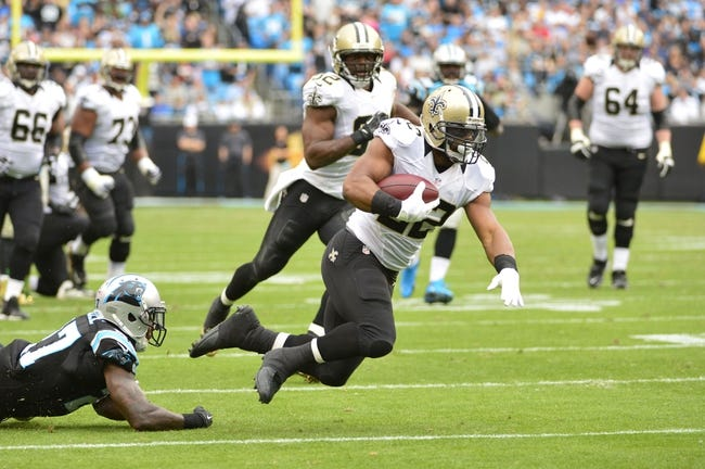 Dec 22, 2013; Charlotte, NC, USA; New Orleans Saints running back Mark Ingram (22) runs as Carolina Panthers strong safety Quintin Mikell (27) defends in the second quarter at Bank of America Stadium. Mandatory Credit: Bob Donnan-USA TODAY Sports