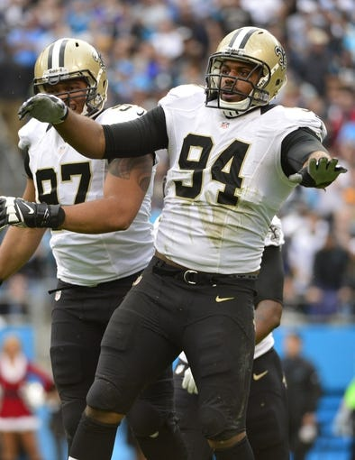 Dec 22, 2013; Charlotte, NC, USA; New Orleans Saints defensive end Cameron Jordan (94) reacts with defensive end Glenn Foster (97) in the second quarter at Bank of America Stadium. Mandatory Credit: Bob Donnan-USA TODAY Sports
