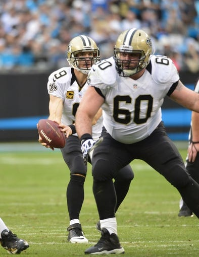 Dec 22, 2013; Charlotte, NC, USA; New Orleans Saints quarterback Drew Brees (9) takes the snap as center Brian De La Puente (60) blocks in the second quarter at Bank of America Stadium. Mandatory Credit: Bob Donnan-USA TODAY Sports