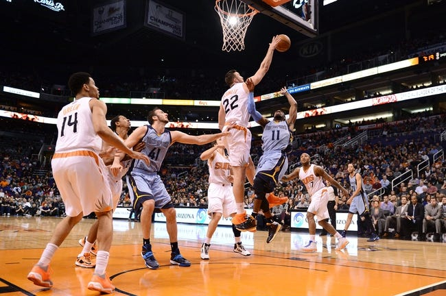 Jan 2, 2014; Phoenix, AZ, USA; Memphis Grizzlies guard Mike Conley (11) is blocked by Phoenix Suns forward Miles Plumlee (22) in the first half at US Airways Center. Mandatory Credit: Jennifer Stewart-USA TODAY Sports