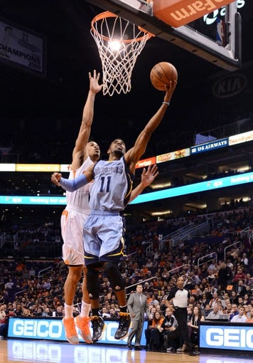 Jan 2, 2014; Phoenix, AZ, USA; Memphis Grizzlies guard Mike Conley (11) lays up the ball against the Phoenix Suns guard Gerald Green (14) in the first half at US Airways Center.  The Grizzlies won 99-91. Mandatory Credit: Jennifer Stewart-USA TODAY Sports
