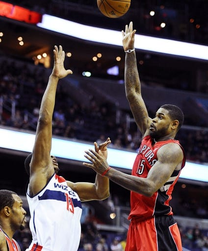 Jan 3, 2014; Washington, DC, USA; Toronto Raptors power forward Amir Johnson (15) attempts a shot over Washington Wizards center Kevin Seraphin (13) during the second half at Verizon Center. The Raptors defeated the Wizards 101 - 88. Mandatory Credit: Brad Mills-USA TODAY Sports