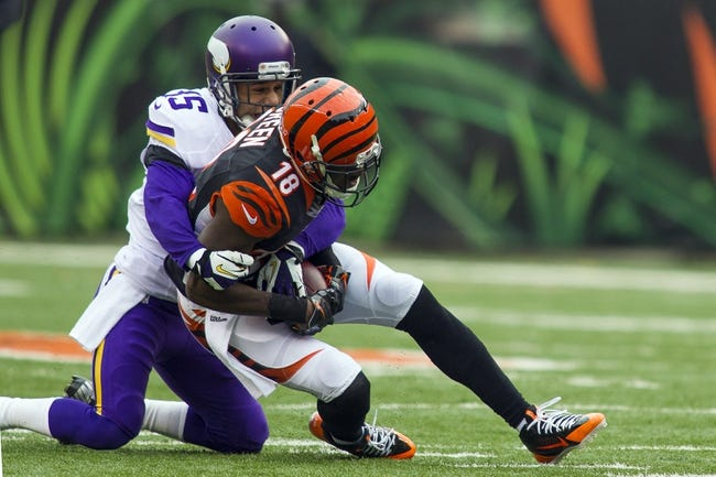 Dec 22, 2013; Cincinnati, OH, USA;   Cincinnati Bengals wide receiver A.J. Green (18) is tackled after a catch by Minnesota Vikings cornerback Marcus Sherels (35) in the fourth quarter of the game at Paul Brown Stadium. Cincinnati Bengals beat the Minnesota Vikings by the score of 42-14. Mandatory Credit: Trevor Ruszkowksi-USA TODAY Sports