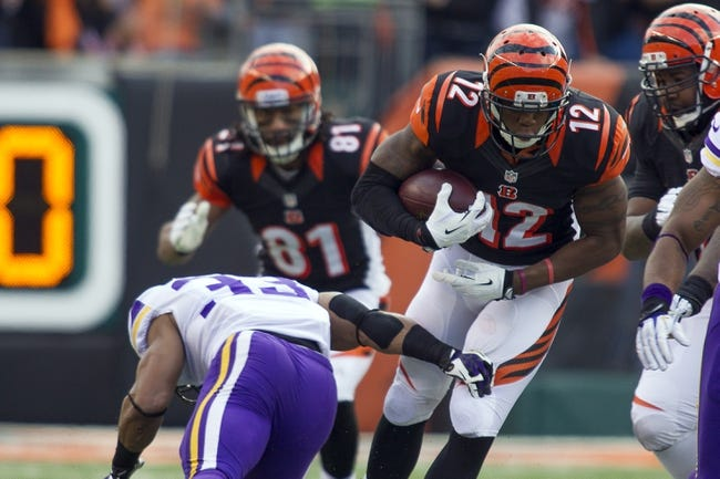 Dec 22, 2013; Cincinnati, OH, USA; Cincinnati Bengals wide receiver Mohamed Sanu (12) runs through the arm tackle of Minnesota Vikings strong safety Jamarca Sanford (33) in the game at Paul Brown Stadium. Cincinnati Bengals beat the Minnesota Vikings by the score of 42-14. Mandatory Credit: Trevor Ruszkowksi-USA TODAY Sports