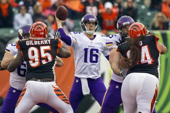 Dec 22, 2013; Cincinnati, OH, USA;  Minnesota Vikings quarterback Matt Cassel (16) passes the ball over Cincinnati Bengals defensive end Wallace Gilberry (95) and defensive tackle Domata Peko (94) in the game at Paul Brown Stadium. Cincinnati Bengals beat the Minnesota Vikings by the score of 42-14. Mandatory Credit: Trevor Ruszkowksi-USA TODAY Sports