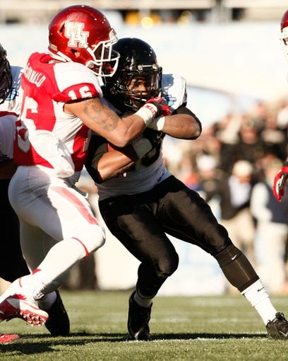 Jan 4, 2014; Birmingham, AL, USA;  Vanderbilt Commodores running back Brian Kimbrow (25) is tackled by Houston Cougars punter Richie Leone (15) during the 2014 Compass Bowl at Legion Field. The Commodores defeated the Cougars 41-24. Mandatory Credit: Marvin Gentry-USA TODAY Sports