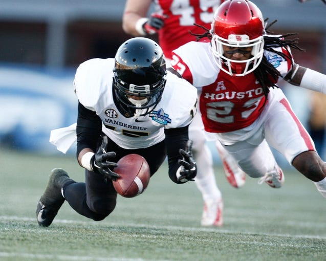 Jan 4, 2014; Birmingham, AL, USA;  Vanderbilt Commodores wide receiver DeAndre Woods (15) goes for a fumbled punt as Houston Cougars defensive back Trevon Stewart (23) goes for the ball also during the 2014 Compass Bowl at Legion Field. The Commodores defeated the Cougars 41-24. Mandatory Credit: Marvin Gentry-USA TODAY Sports