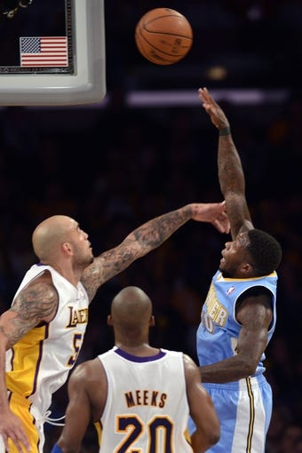 Jan 5, 2014; Los Angeles, CA, USA; Denver Nuggets guard Nate Robinson (10) attempts a shot defended by Los Angeles Lakers center Robert Sacre (50) during the fourth period at Staples Center. The Denver Nuggets defeated the Los Angeles Lakers 137-115. Mandatory Credit: Kelvin Kuo-USA TODAY Sports