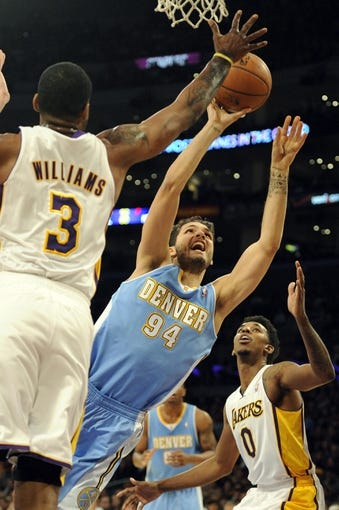 Jan 5, 2014; Los Angeles, CA, USA; Denver Nuggets guard Evans Foumier (94) attempts a shot defended by Los Angeles Lakers forward Shawne Williams (3) during the first period at Staples Center. Mandatory Credit: Kelvin Kuo-USA TODAY Sports