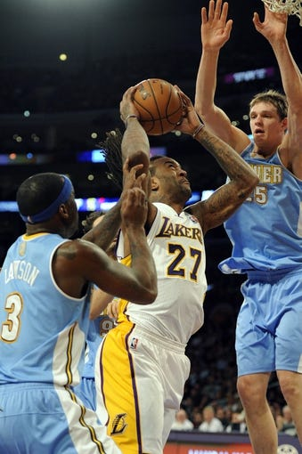 Jan 5, 2014; Los Angeles, CA, USA; Los Angeles Lakers center Jordan Hill (27) goes up for a shot defended by Denver Nuggets guard Ty Lawson (3) and Denver Nuggets center Timofey Mozgov (25) during the third period at Staples Center. The Denver Nuggets defeated the Los Angeles Lakers 137-115. Mandatory Credit: Kelvin Kuo-USA TODAY Sports