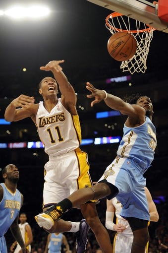 Jan 5, 2014; Los Angeles, CA, USA; Los Angeles Lakers guard Wesley Johnson (11) is fouled by Denver Nuggets forward Kenneth Faried (35) after going up for a rebound during the third period at Staples Center. The Denver Nuggets defeated the Los Angeles Lakers 137-115. Mandatory Credit: Kelvin Kuo-USA TODAY Sports