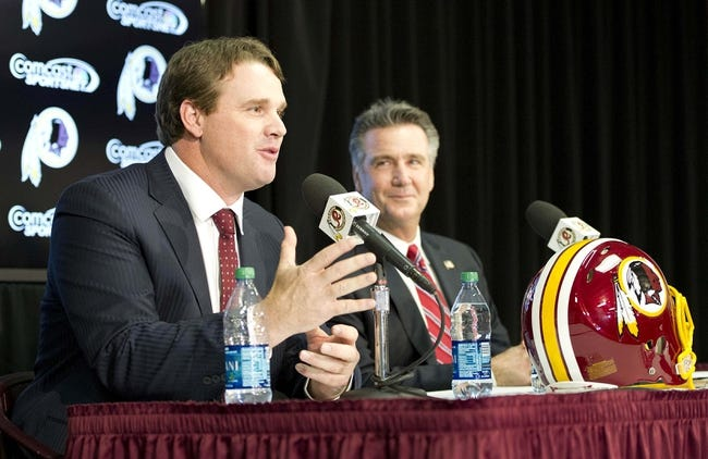 Jan 9, 2014; Ashburn, VA, USA; Washington Redskins head coach Jay Gruden speaks as general manager Bruce Allen looks on during a press conferences at Redskins Park Team Auditorium. Mandatory Credit: Brad Mills-USA TODAY Sports