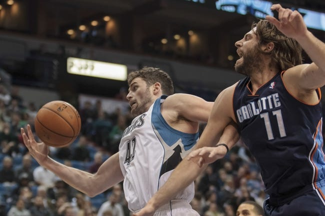 Jan 10, 2014; Minneapolis, MN, USA; Minnesota Timberwolves power forward Kevin Love (42) gets the rebound around Charlotte Bobcats forward Josh McRoberts (11) in the first quarter against the at Target Center. Mandatory Credit: Brad Rempel-USA TODAY Sports