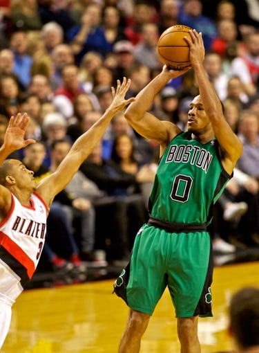 Jan 11, 2014; Portland, OR, USA; Boston Celtics point guard Avery Bradley (0) shoots over Portland Trail Blazers shooting guard C.J. McCollum (3) at the Moda Center. Mandatory Credit: Craig Mitchelldyer-USA TODAY Sports