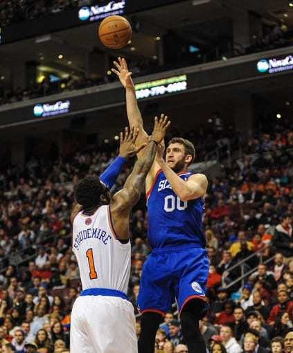 Jan 11, 2014; Philadelphia, PA, USA; Philadelphia 76ers center Spencer Hawes (00) takes a shot as  New York Knicks power forward Amar'e Stoudemire (1) defends during the game at the Wells Fargo Center. The New York Knicks won 102-92.Mandatory Credit: John Geliebter-USA TODAY Sports