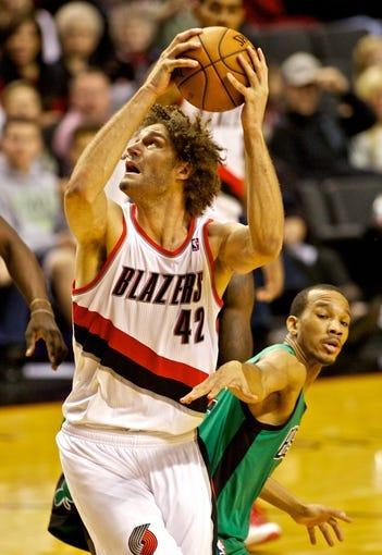 Jan 11, 2014; Portland, OR, USA; Portland Trail Blazers center Robin Lopez (42) shoots over Boston Celtics point guard Avery Bradley (0) at the Moda Center. Mandatory Credit: Craig Mitchelldyer-USA TODAY Sports