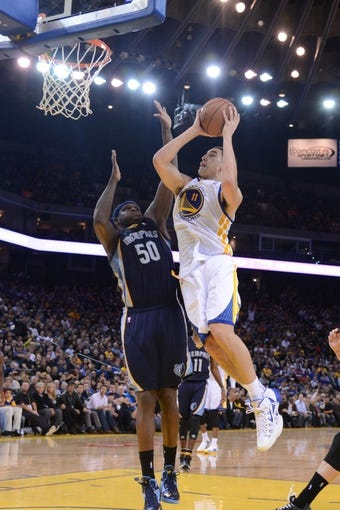 November 20, 2013; Oakland, CA, USA; Golden State Warriors shooting guard Klay Thompson (11) shoots the basketball against Memphis Grizzlies power forward Zach Randolph (50) during the fourth quarter at Oracle Arena. The Grizzlies defeated the Warriors 88-81 in overtime. Mandatory Credit: Kyle Terada-USA TODAY Sports