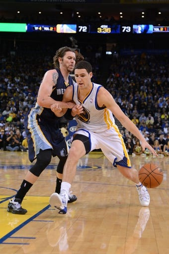 November 20, 2013; Oakland, CA, USA; Golden State Warriors shooting guard Klay Thompson (11, right) dribbles the basketball against Memphis Grizzlies small forward Mike Miller (13, left) during the fourth quarter at Oracle Arena. The Grizzlies defeated the Warriors 88-81 in overtime. Mandatory Credit: Kyle Terada-USA TODAY Sports
