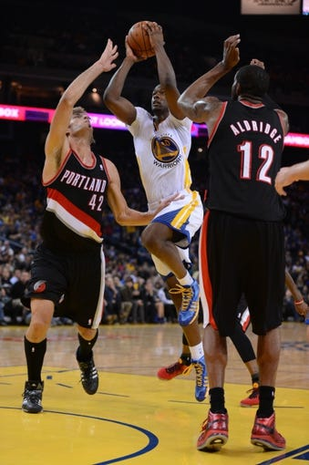 November 23, 2013; Oakland, CA, USA; Golden State Warriors small forward Harrison Barnes (40) drives to the basket against Portland Trail Blazers center Robin Lopez (42) and power forward LaMarcus Aldridge (12) during the fourth quarter at Oracle Arena. The Trail Blazers defeated the Warriors 113-101. Mandatory Credit: Kyle Terada-USA TODAY Sports