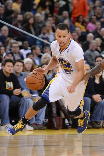 November 23, 2013; Oakland, CA, USA; Golden State Warriors point guard Stephen Curry (30) dribbles the basketball during the third quarter against the Portland Trail Blazers at Oracle Arena. The Trail Blazers defeated the Warriors 113-101. Mandatory Credit: Kyle Terada-USA TODAY Sports