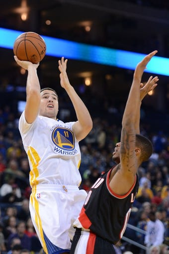 November 23, 2013; Oakland, CA, USA; Golden State Warriors shooting guard Klay Thompson (11) shoots the basketball against Portland Trail Blazers point guard Damian Lillard (0) during the third quarter at Oracle Arena. The Trail Blazers defeated the Warriors 113-101. Mandatory Credit: Kyle Terada-USA TODAY Sports