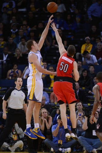 December 3, 2013; Oakland, CA, USA; Golden State Warriors power forward David Lee (10, left) shoots the basketball against Toronto Raptors power forward Tyler Hansbrough (50) during the first quarter at Oracle Arena. The Warriors defeated the Raptors 112-103. Mandatory Credit: Kyle Terada-USA TODAY Sports