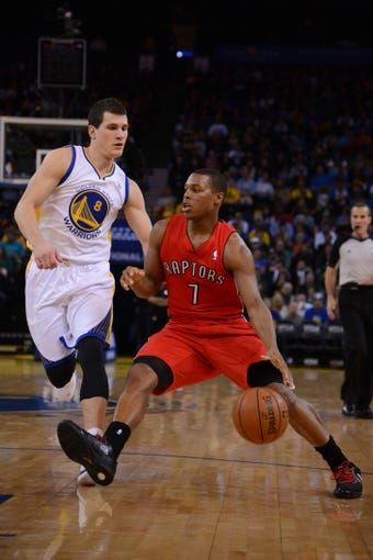 December 3, 2013; Oakland, CA, USA; Toronto Raptors point guard Kyle Lowry (7) dribbles the basketball against Golden State Warriors point guard Nemanja Nedovic (8) during the first quarter at Oracle Arena. The Warriors defeated the Raptors 112-103. Mandatory Credit: Kyle Terada-USA TODAY Sports