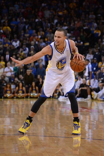 December 3, 2013; Oakland, CA, USA; Golden State Warriors point guard Stephen Curry (30) dribbles the basketball during the fourth quarter against the Toronto Raptors at Oracle Arena. The Warriors defeated the Raptors 112-103. Mandatory Credit: Kyle Terada-USA TODAY Sports