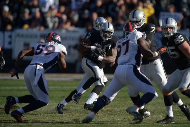 Dec 29, 2013; Oakland, CA, USA; Oakland Raiders running back Darren McFadden (20) carries the ball against the Denver Broncos at O.co Coliseum. The Broncos defeated the Raiders 34-14. Mandatory Credit: Kirby Lee-USA TODAY Sports