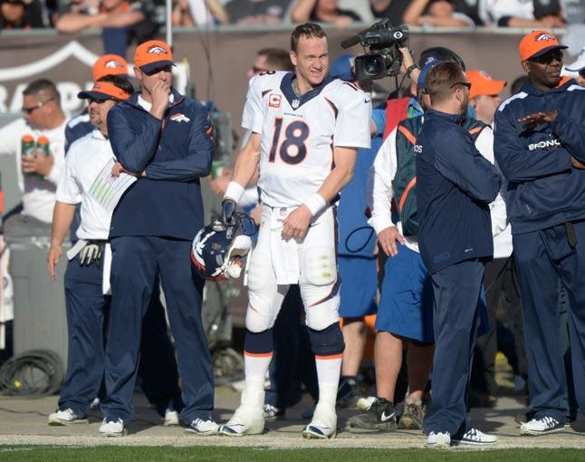 Dec 29, 2013; Oakland, CA, USA; Denver Broncos quarterback Peyton Manning (18) reacts after setting the NFL single season passing yardage record in the second quarter against the Oakland Raiders at O.co Coliseum. Mandatory Credit: Kirby Lee-USA TODAY Sports