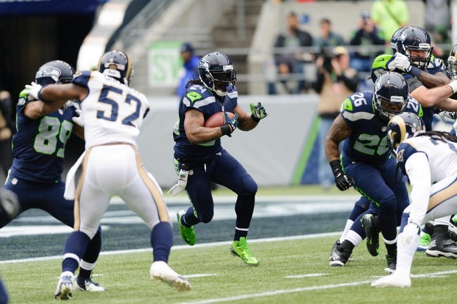 Dec 29, 2013; Seattle, WA, USA; Seattle Seahawks running back Marshawn Lynch (24) carries the ball against the St. Louis Rams during the game at CenturyLink Field. Seattle defeated St. Louis 27-9. Mandatory Credit: Steven Bisig-USA TODAY Sports