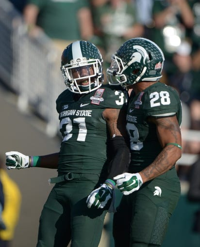 Jan 1, 2014; Pasadena, CA, USA; Michigan State Spartans cornerack Darqueze Dennard (31) and linebacker Denicos Allen (28) celebrate during the 100th Rose Bowl against the Stanford Cardinal. Mandatory Credit: Kirby Lee-USA TODAY Sports
