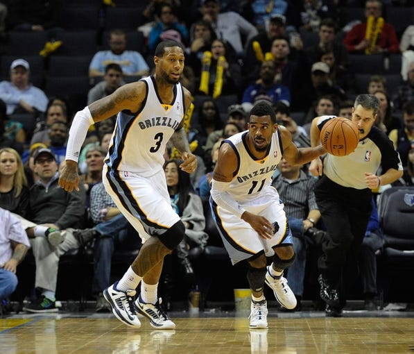 Jan 7, 2014; Memphis, TN, USA; Memphis Grizzlies point guard Mike Conley (11) brings the ball up court against the San Antonio Spurs at FedExForum. the San Antonio Spurs beat the Memphis Grizzlies 110 - 108 Mandatory Credit: Justin Ford-USA TODAY Sports
