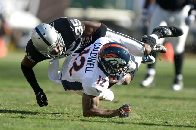 Dec 29, 2013; Oakland, CA, USA; Oakland Raiders cornerback Chimdi Chekwa (35) tackles Denver Broncos receiver Andre Caldwell (12) at O.co Coliseum. The Broncos defeated the Raiders 34-14. Mandatory Credit: Kirby Lee-USA TODAY Sports