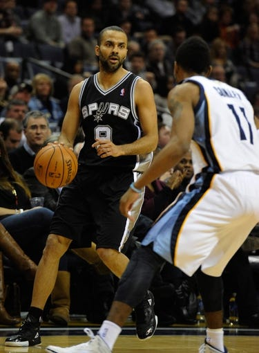 Jan 7, 2014; Memphis, TN, USA; San Antonio Spurs point guard Tony Parker (9) handles the ball against Memphis Grizzlies point guard Mike Conley (11) during the first quarter at FedExForum. the San Antonio Spurs beat the Memphis Grizzlies 110 - 108 Mandatory Credit: Justin Ford-USA TODAY Sports
