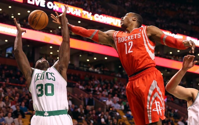Jan 13, 2014; Boston, MA, USA; Houston Rockets power forward Dwight Howard (12) reaches for a rebound over Boston Celtics power forward Brandon Bass (30) during the first quarter at TD Garden. Mandatory Credit: Winslow Townson-USA TODAY Sports