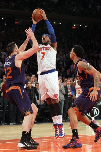 Jan 13, 2014; New York, NY, USA; New York Knicks small forward Carmelo Anthony (7) shoots over Phoenix Suns center Miles Plumlee (22) and Phoenix Suns shooting guard Gerald Green (14) during the fourth quarter of a game at Madison Square Garden. The Knicks defeated the Suns 98-96 in overtime. Mandatory Credit: Brad Penner-USA TODAY Sports
