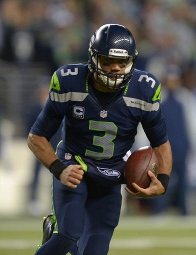 Dec 2, 2013; Seattle, WA, USA; Seattle Seahawks quarterback Russell Wilson (3) carries the ball against the New Orleans Saints at CenturyLink Field. The Seahawks defeated the Saints 34-7. Mandatory Credit: Kirby Lee-USA TODAY Sports