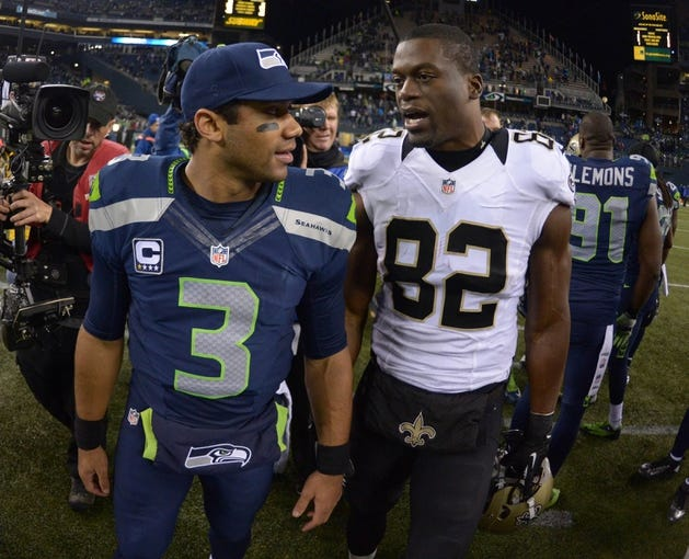 Dec 2, 2013; Seattle, WA, USA; Seattle Seahawks quarterback Russell Wilson (left) and New Orleans Saints tight end Benjamin Watson (82) after the game at CenturyLink Field. The Seahawks defeated the Saints 34-7. Mandatory Credit: Kirby Lee-USA TODAY Sports