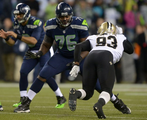 Dec 2, 2013; Seattle, WA, USA; Seattle Seahawks tackle Russell Okung (76) defends against New Orleans Saints linebacker Junior Galette (93) at CenturyLink Field. The Seahawks defeated the Saints 34-7. Mandatory Credit: Kirby Lee-USA TODAY Sports