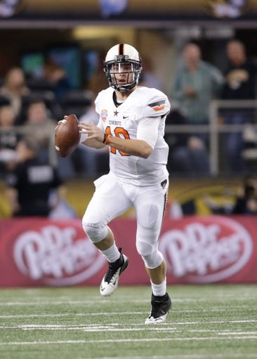 Jan 3, 2014; Arlington, TX, USA; Oklahoma State Cowboys quarterback Clint Chelf (10) throws a pass in the first quarter of the game against the Missouri Tigers at the 2014 Cotton Bowl at AT&T Stadium. Missouri beat Oklahoma State 41-31. Mandatory Credit: Tim Heitman-USA TODAY Sports