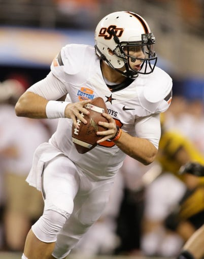 Jan 3, 2014; Arlington, TX, USA; Oklahoma State Cowboys quarterback Clint Chelf (10) rolls out to pass against the Missouri Tigers in the first quarter at the 2014 Cotton Bowl at AT&T Stadium. Missouri beat Oklahoma State 41-31. Mandatory Credit: Tim Heitman-USA TODAY Sports
